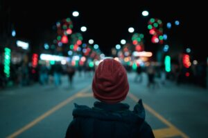 boy in wool hat looking down a city street that's decorated with Christmas lights and ornaments